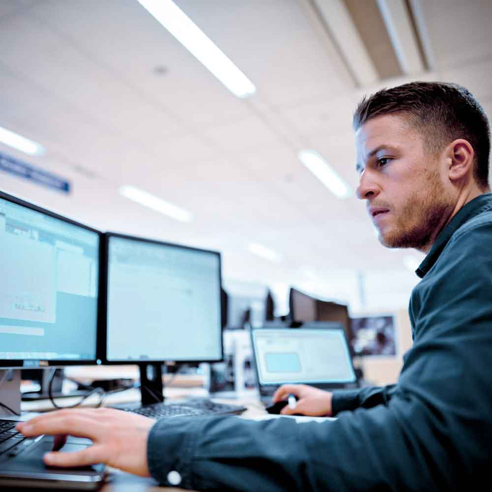 A man sits in front of three screens in the Volvo Trucks International Uptime Center